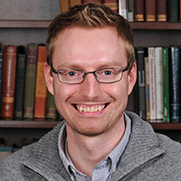 Derrick Wirtz, a man with short red hair and thin-rimmed glasses, smiling in front of a bookcase.