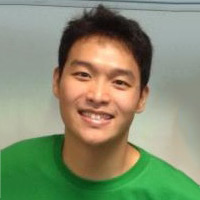Bob Sim, a student with short brown hair, smiling in front of a white wall.