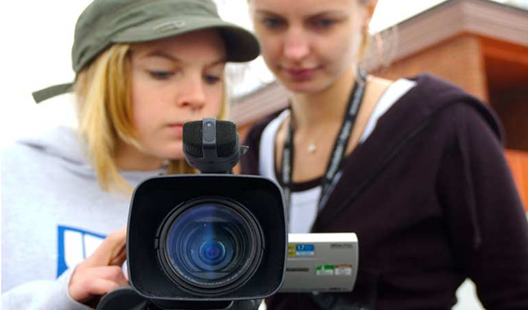 Two female students looking into the LCD screen of a video camera.