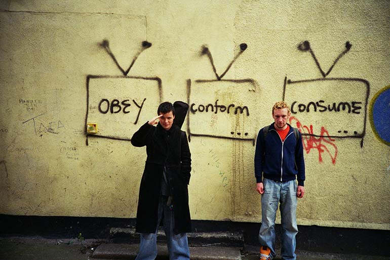 "Two adolescent males standing in front of a wall graffitied with the words ""Obey"", ""Conform"", and ""Consume""."