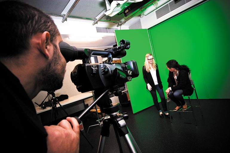 Two female students being filmed in front of a green screen.