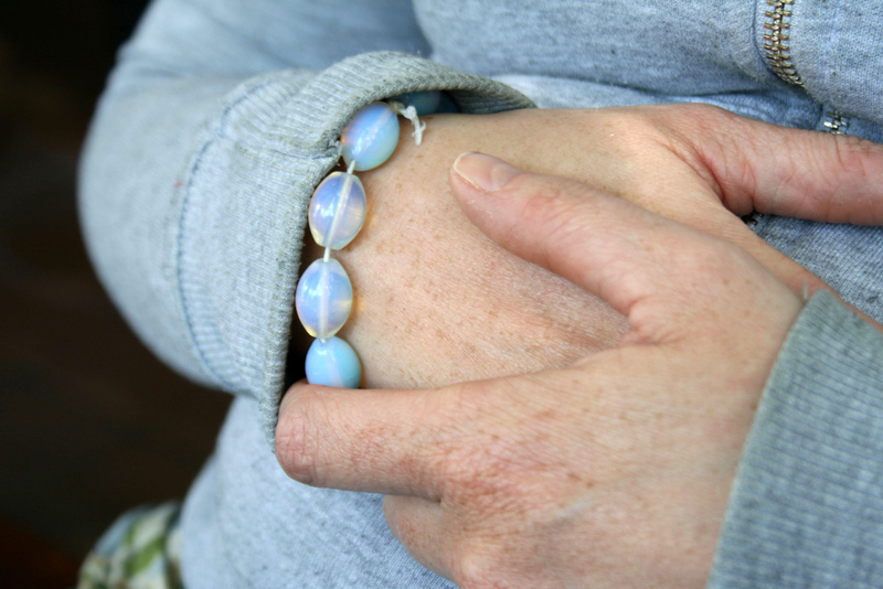 A close up of a woman clutching her hands together.