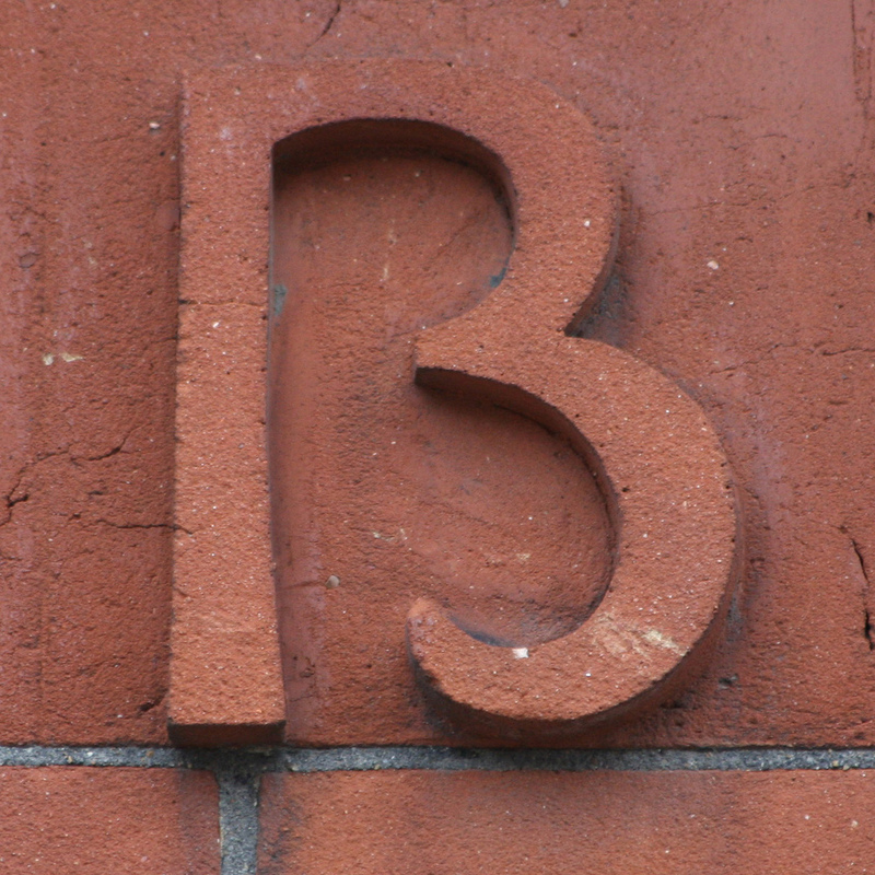 Close up image of the marking on the side of a building. It isn't clear if the marking is the number 13 or the letter B.