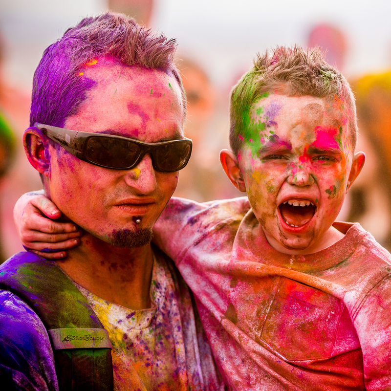 A father and son smile and shout after finishing an exciting race called The Color Run. Both are covered from head to toe in many shades of brightly colored powder.