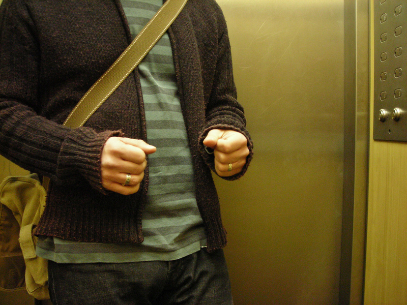 A man nervously clenches his fists inside an elevator.