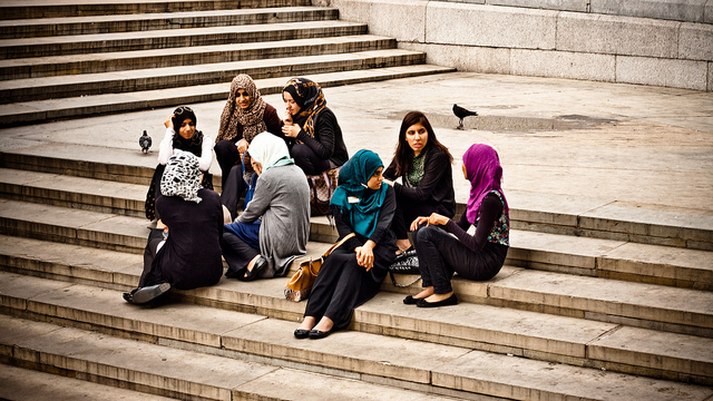 Two groups of teenage girls, most of whom are wearing head scarves, sitting and chatting on some steps.