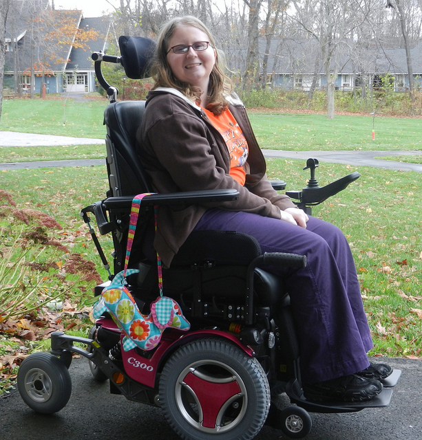 A smiling woman in a motorized wheelchair.