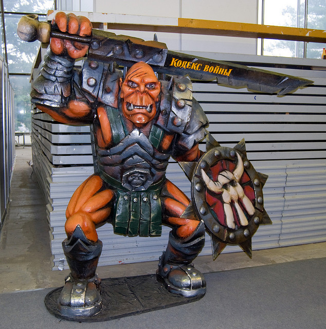 An Orc from the video game Fantasy Wars holds a giant sword over its head.