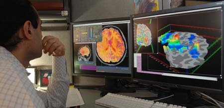 A researcher studies fMRI images on a computer monitor.