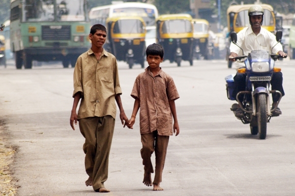 Two boys walk together down a busy street in Bangalore, India while holding hands.