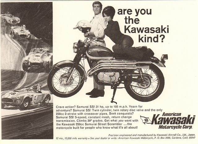 "An advertisement for Kawasaki motorcycles from the 1970's. The slogan is ""Are You the Kawasaki Kind?"" The ad features an average looking man dressed in a shirt and tie standing behind a Kawasaki motorcycle and holding a motorcycle helmet. An attractive woman sits on the seat of the motorcycle and leans her head on the man's shoulder."