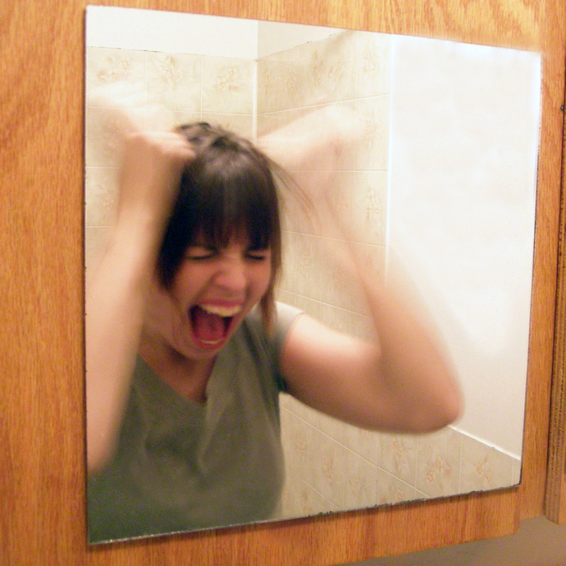 A woman stands in front of a mirror screaming and pulling her own hair.
