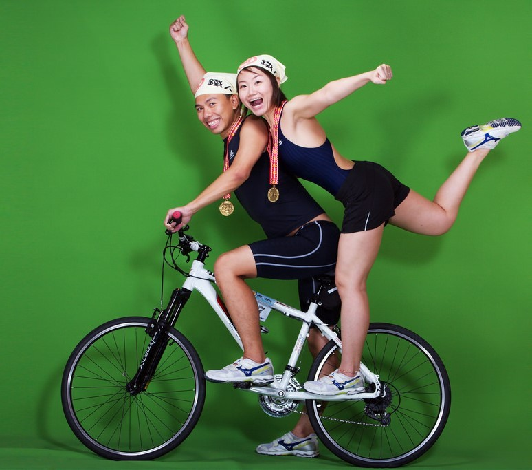 An young, athletic couple pose for photos on their bike while wearing medals they've won in competition.