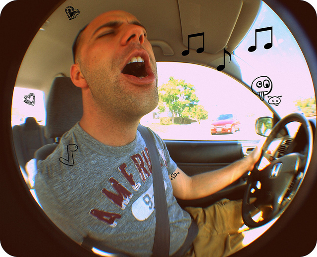 A young man sits behind the wheel of a car with his eyes closed as he sings along with the radio.