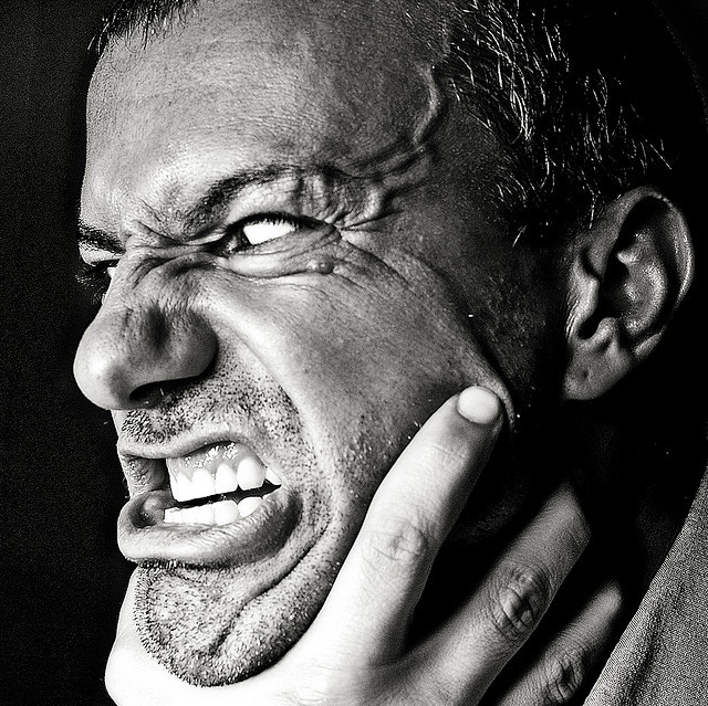 A man with an enraged look on his face and bulging veins on his forehead strains against a hand that is chocking him.