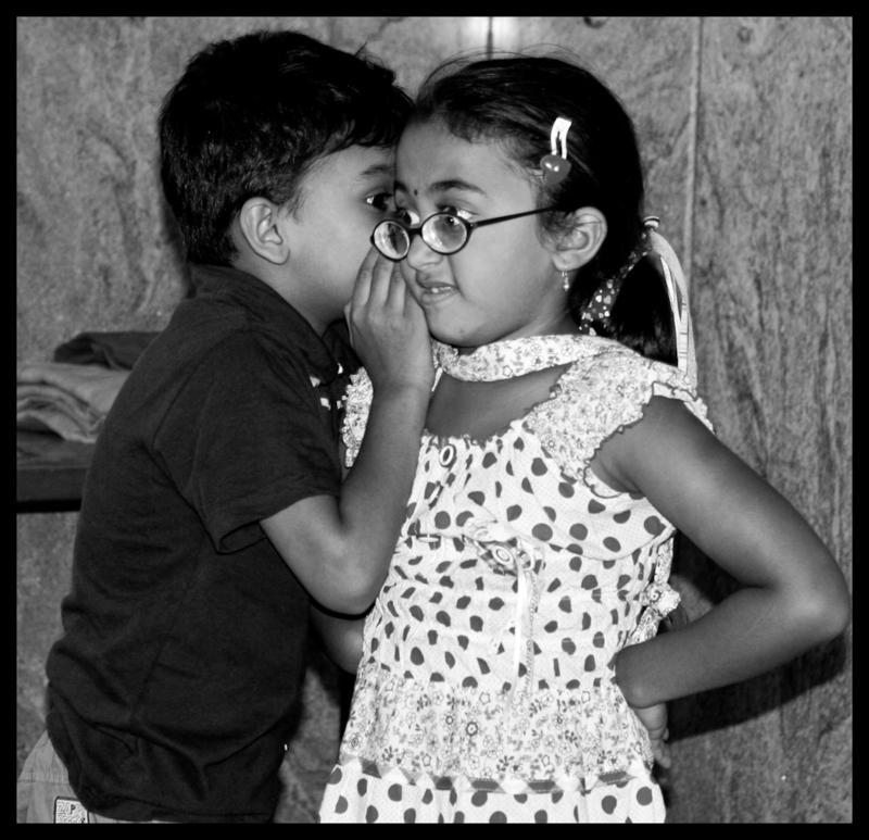 A young boy whispers in the ear of a young girl.