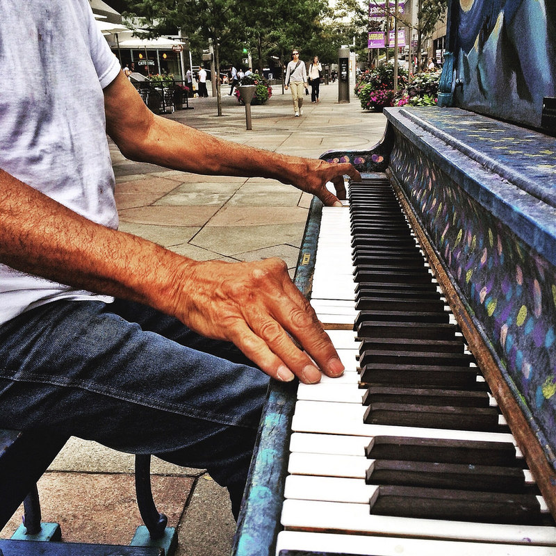 A man plays a piano on a sidewalk.