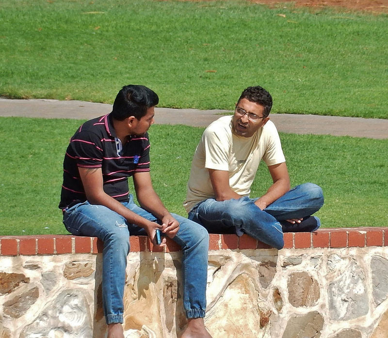 Two young men sit together outside on a sunny day having a conversation.