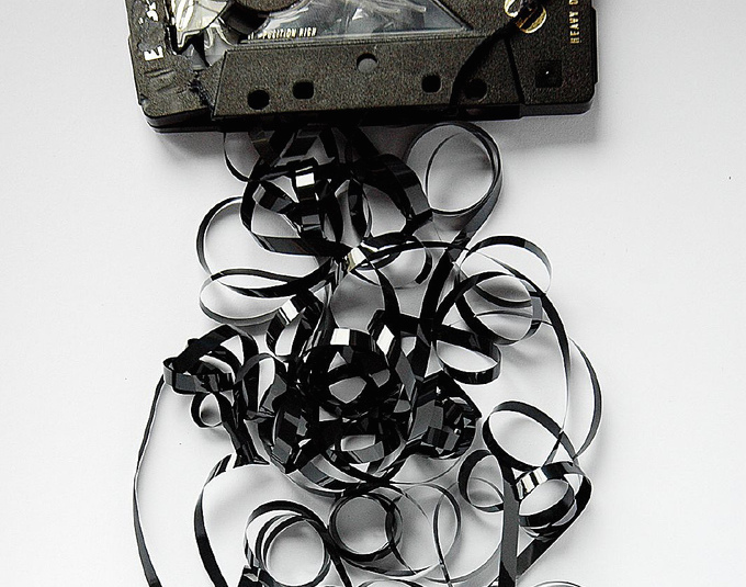 A broken audio cassette tape sits on a table with tape spilling out into a messy pile.