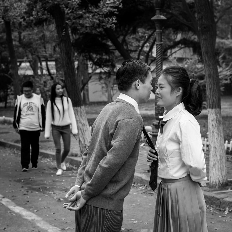 A young man and woman dressed in school uniforms are just about to kiss.