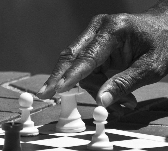 A chess player with his hand on a rook.