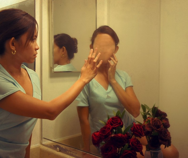 A woman looks into the mirror and sees a faceless reflection.