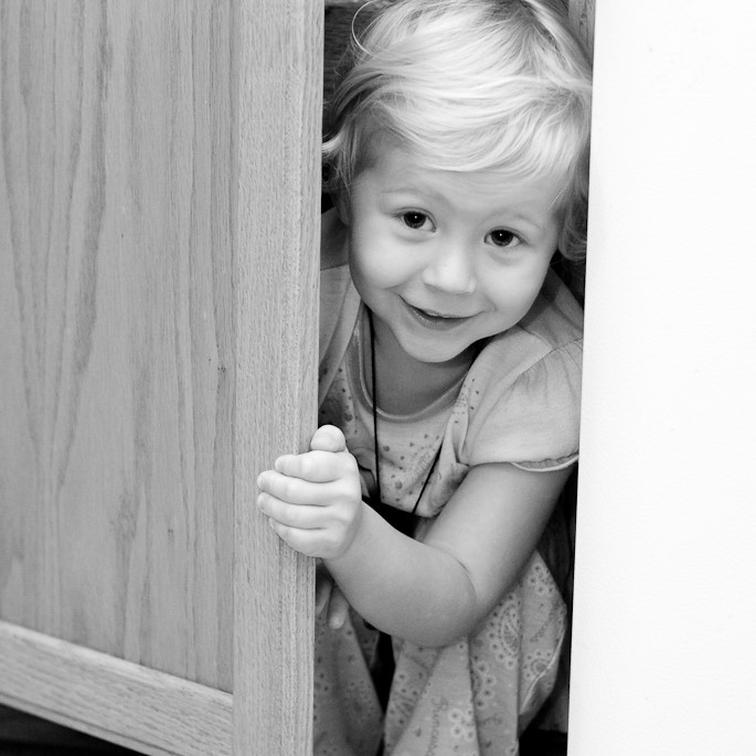 A young girl smiles as she peeks out from a hiding place.