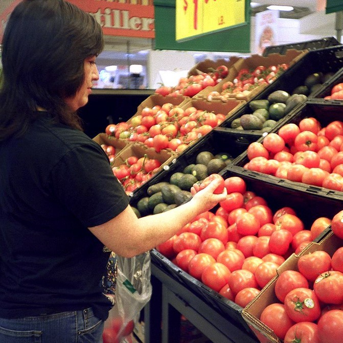 A woman inspects tomatoes as she puts them into a shopping bag.