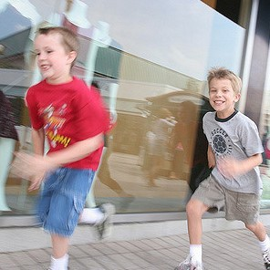 Two young boys sprint along the sidewalk.