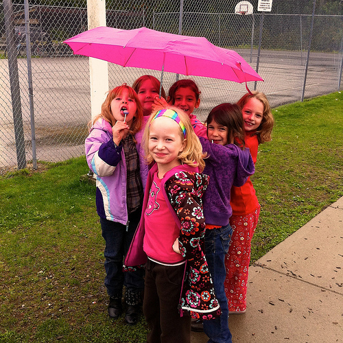 A group of young girls stand together under an umbrella on the playground.