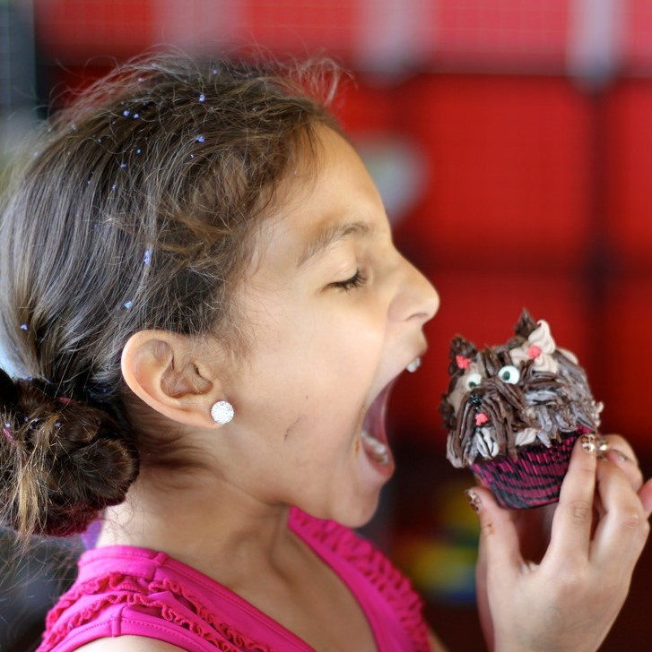 A girls prepares to take a big bite out of a cupcake.