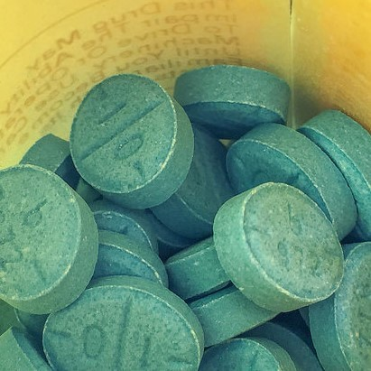Green Adderall pills in a prescription bottle.