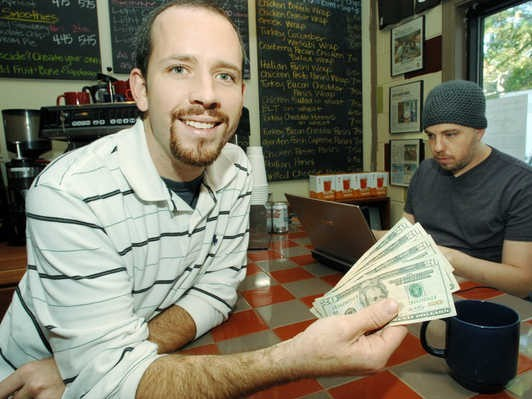Coffee shop owner Josh cooks shows 100 dollars that were donated by a generous customer to buy drinks for strangers.