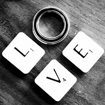 "Scrabble tiles and wedding rings spell out the word ""Love""."