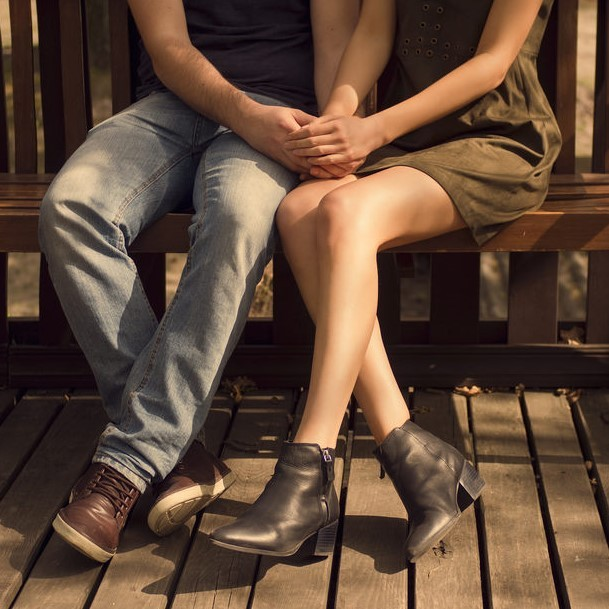 A couple holding hands on a bench.