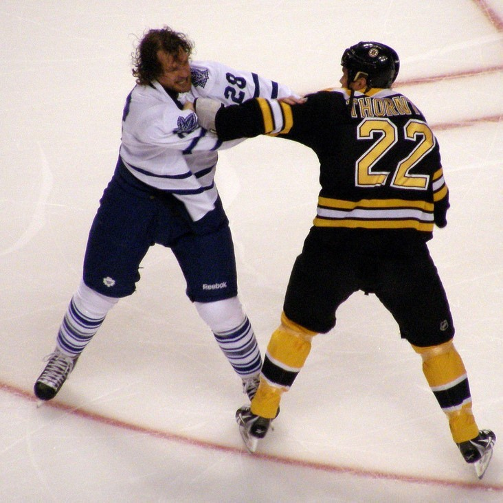 Two professional hockey players fight during a game.