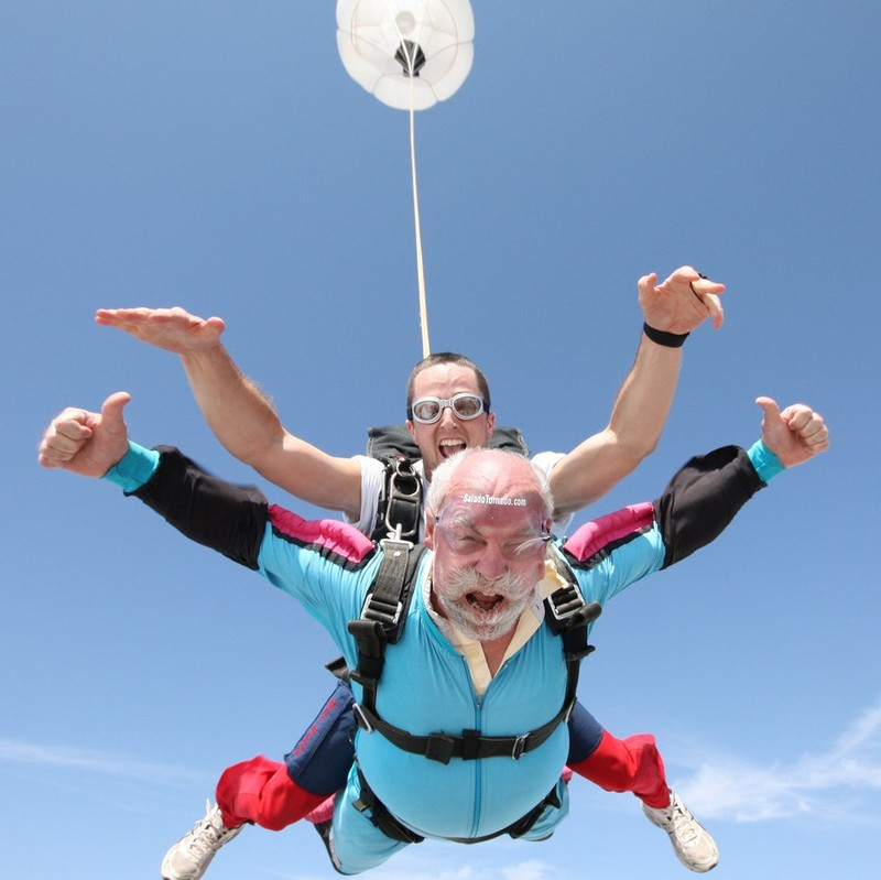 An older man with white hair and beard skydives in tandem with a younger jumpmaster.