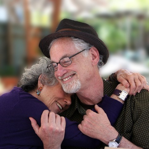 A grey-haired couple share an affectionate hug.