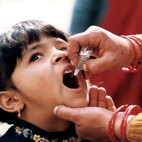 A girl opens her mouth to receive an oral vaccination.