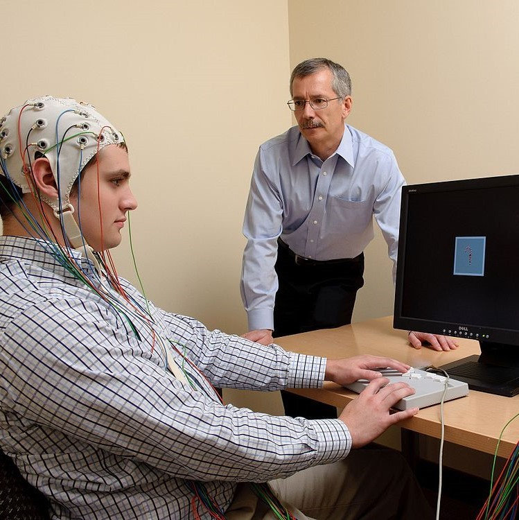 A study participant wears an EEG cap and uses a touch pad to react to images on a computer screen. An experimenter stands by observing.
