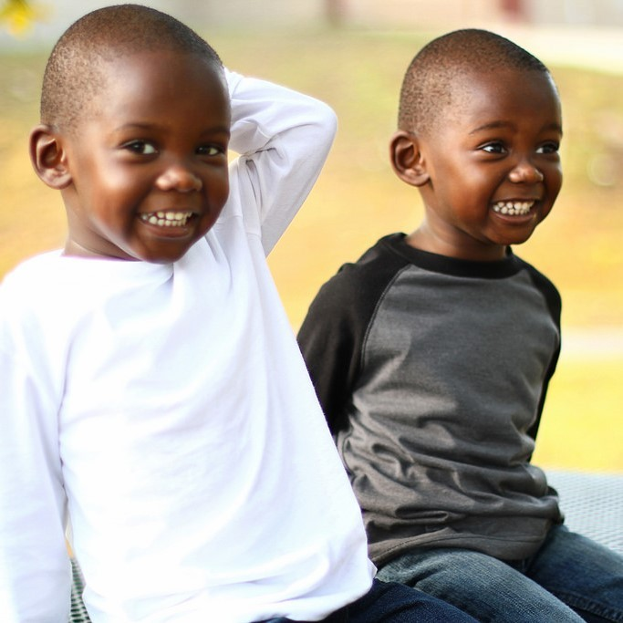 Two young twin brothers sit together and smile.
