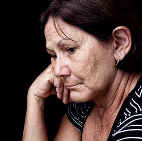 An older woman rests her head on her hand with a sad look on her face.