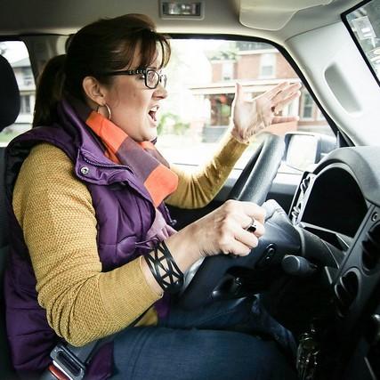 A woman shouts and makes an aggressive hand gesture as she drives her car.