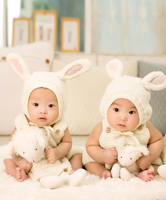 Twin boys sit together dressed in matching clothes and hats and holding similar stuffed animals.
