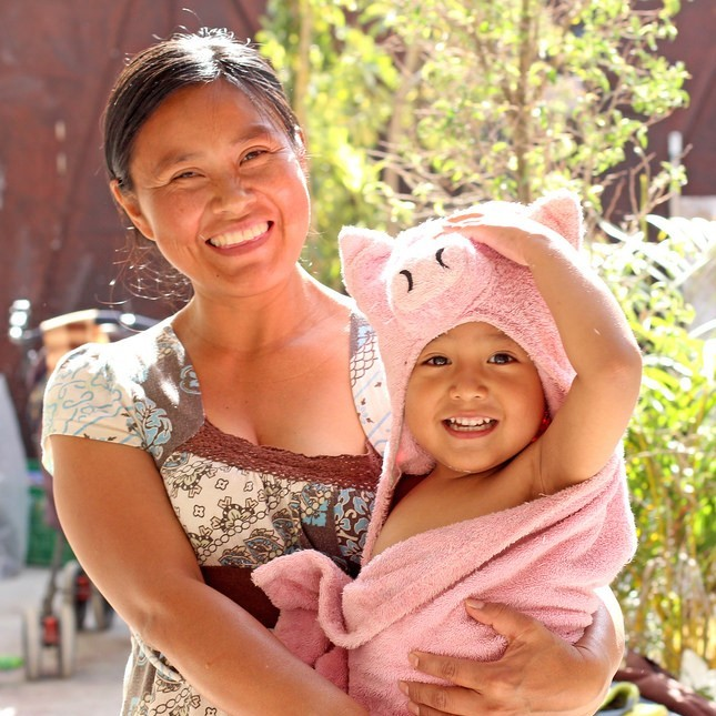 A smiling mother holds her happy toddler in a towel after a bath.