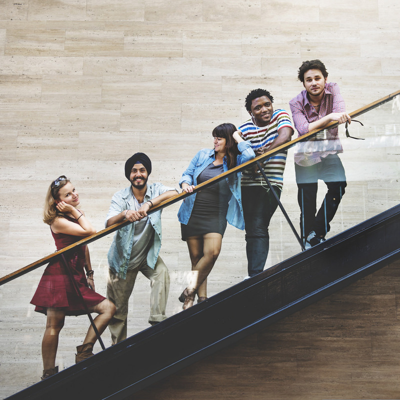 A group of young adult friends stand together on a staircase.