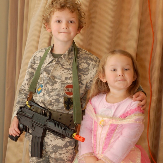 A brother and sister stand side by side. He is dressed in a camouflage military uniform and is holding a toy gun. She is dressed in a pretty pink princess dress.