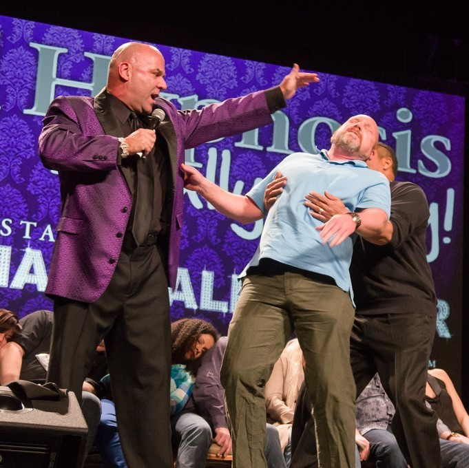 A stage hypnotist holds his hand over the head of a volunteer who falls limp into the arms of the hypnotist's assistant. A group of volunteers seem to be unconscious in their seats in the background.