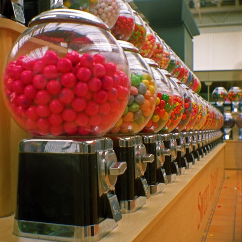 A row of coin-operated gumball machines.