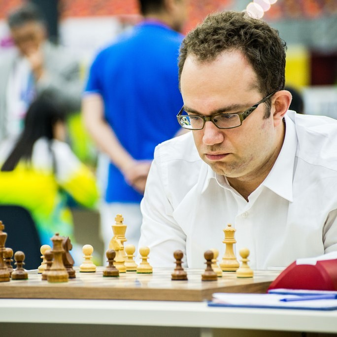 A man sits hunched over looking at the pieces on a chessboard with an expression of deep concentration on his face.